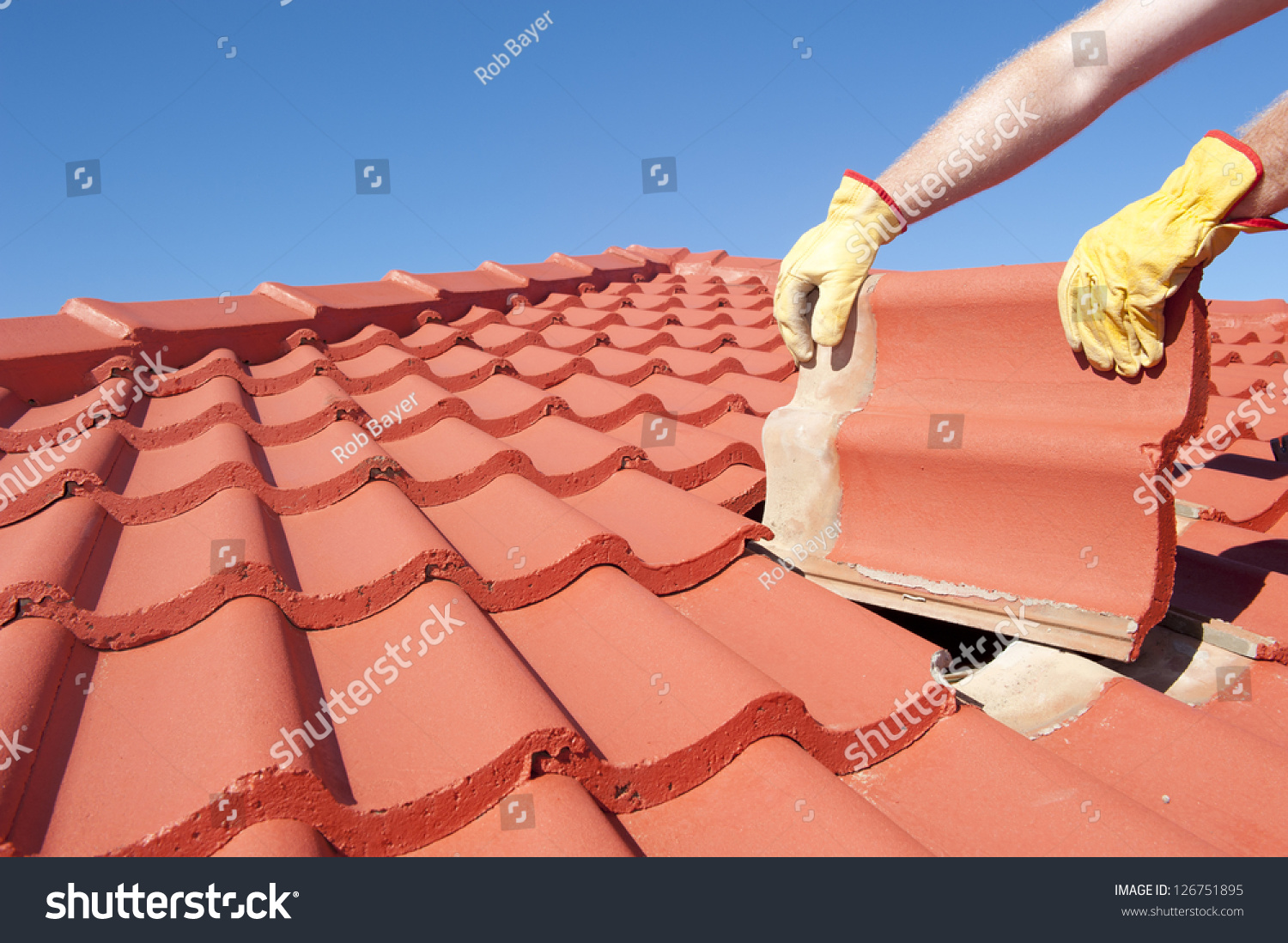 stock-photo-roof-repair-worker-with-yellow-gloves-replacing-red-tiles-or-shingles-on-house-with-blue-sky-as-126751895.jpg